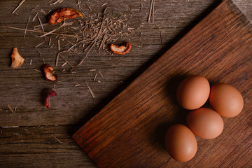 chicken organic eggs on cutting board rustic wooden background