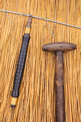 Thatch tools in front of a newly thatched roof
