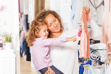Small cute girl with her mother choosing dress