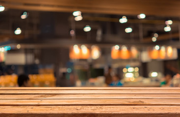 Empty wooden deck table on blurred food court background.