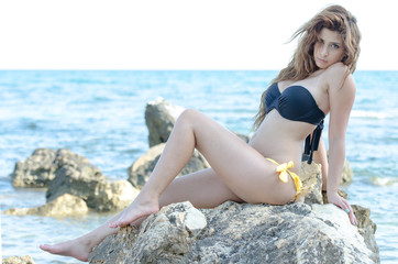 Cute lady in bikini, posing on sea wild rocks