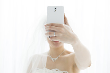 The bride, shooting themselves in the mobile phone