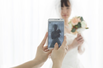 Women who are taking the bride photo on mobile phone