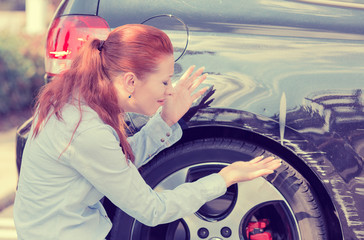 Frustrated woman checking pointing at car scratches dents