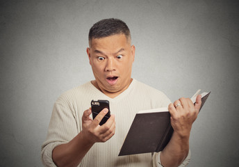 shocked middle aged man looking at phone holding book