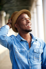 Carefree young african american man smiling with hat