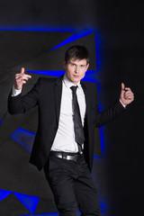 Handsome elegant man in black suit. Success, blue lights