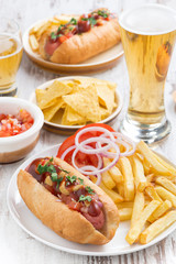 hot dogs with French fries, beer and snacks, vertical