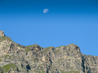 Poster UFO Moonrise over a ridge in the austrian Alps with a clear blue sky