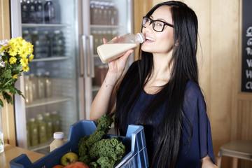 Junge Verkäuferin trinkt Gemüsesaft