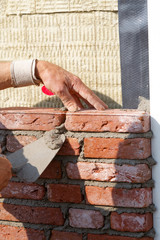 bricklayer builds a wall