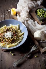 pasta with tomato and peas sauce on plate with parmesan