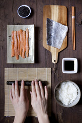 overhead shot of hands rolling sushi and ingredients on table