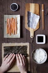 hands rolling sushi and ingredients on table