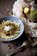 pasta with tomato and peas sauce on plate with parmesan cheese