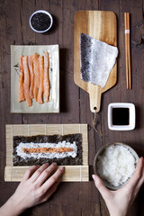 overhead shot of hands rolling sushi