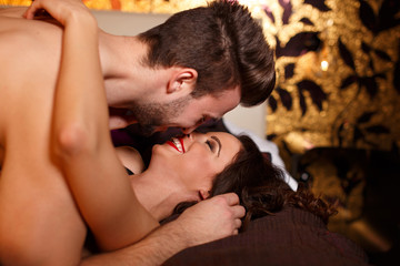 Passionate couple kissing on bed