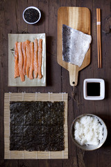 overhead shot of ingredients for preparing sushi on wooden table