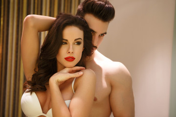 Sensual woman posing in mirror with young boyfriend