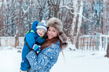 Happy mother and baby playing on snow