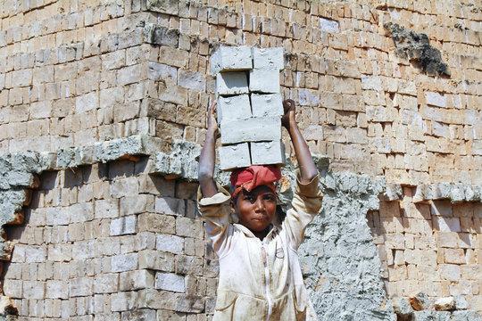 Female worker carry bricks on her head