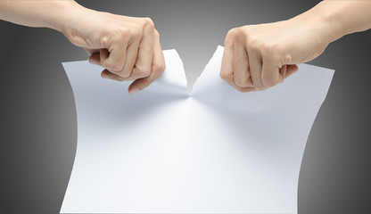 Woman hand ripping white paper on gray background