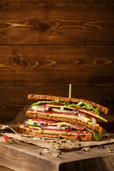 One piece of sandwich on old papper with big cutting board. In v