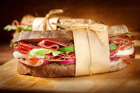 Sandwich with bacon and fresh vegetables on vintage wooden cutti