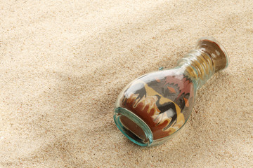 Bottle with sand picture on sand background