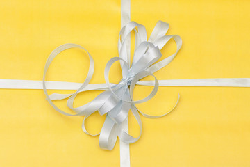 gift in yellow packing with a white bow