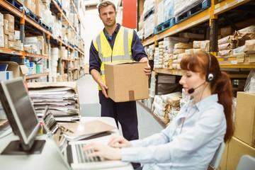 Warehouse manager wearing headset using laptop