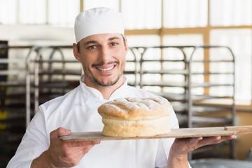 Baker showing a freshly baked loaf