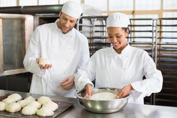 Team of bakers preparing dough