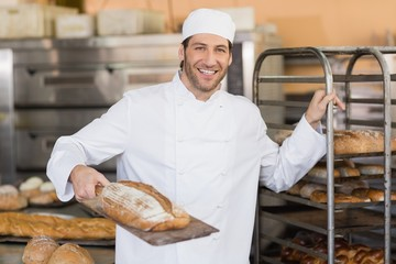 Smiling baker looking at camera holding bread