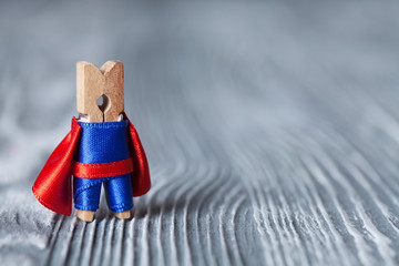 Clothespin superhero in blue suit and red cape.