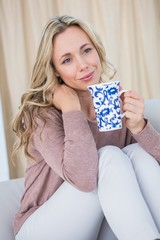 Thoughtful blonde on couch holding cup of coffee