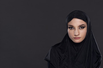 Portrait of a beautiful Muslim woman dressed in black hijab