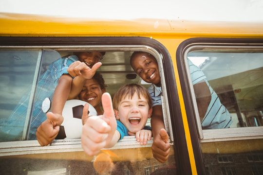 Cute mixed race pupils smiling at camera in the school bus