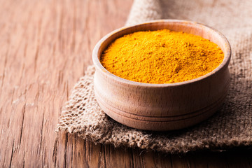 In de dag Kruiden dry spice turmeric in a wooden bowl close-up