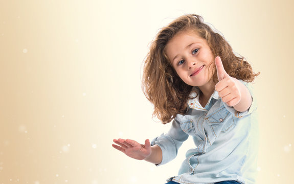 Blonde little girl with thumb up