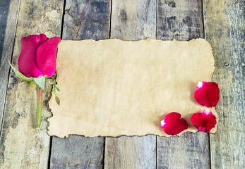 Fresh red rose and old paper on a wooden background.