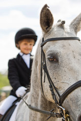 Little girl riding a horse participates in competitions