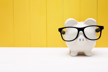 Piggy bank with glasses over yellow wooden wall