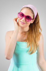 Portrait of cute woman wearing rose-coloured sunglasses
