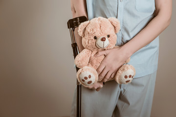 patient on crutches with a children's toy