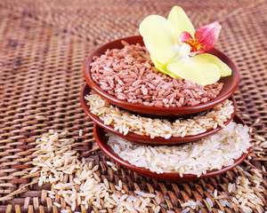 Different types of rice in bowls on wicker background