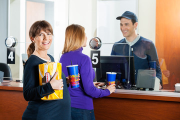 Woman Holding Snacks While Friend Buying Tickets At Box Office