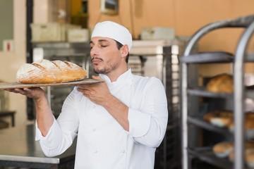 Baker smelling a freshly baked loaf