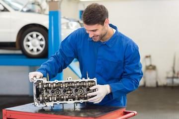 Smiling mechanic working on engine