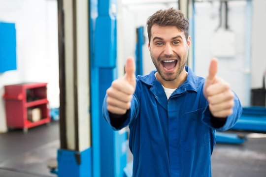 Smiling mechanic showing thumbs up